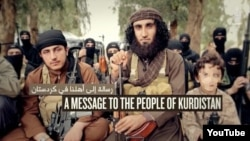 A capture of Kurdish Islamic State (IS) militant Abu Khattab al-Kurdi and his young son (pixelated) from a video purportedly by militant group Islamic State that concludes with the murder of a Kurdish-speaking captive.