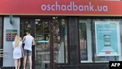 People try to enter a closed branch of Oschadbank in Kyiv on June 27, after many banks were hit by a massive cyberattack.