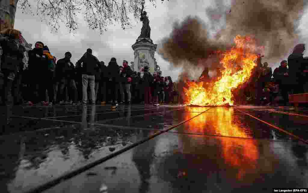 A trashcan burns on Place de la Republique as students demonstrate against the increase of the subscription fees for foreign students in Paris on December 7. (EPA-EFE/Ian Langsdon)