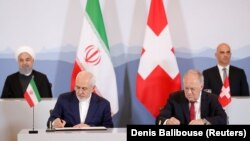 Swiss President Alain Berset (top right) and Iranian President Hassan Rohani (top left) look on as Johann Schneider-Ammann, head of the Federal Department of Economic Affairs, Education and Research (right) and Iran's Foreign Minister Mohammad Javad Zarif sign documents in Bern on July 3.