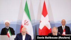 Swiss President Alain Berset and Iranian President Hassan Rohani look on as Johann Schneider-Ammann, Head of the Federal Department of Economic Affairs, Education and research and Iran's Foreign Minister Mohammad Javad Zarif sign documents