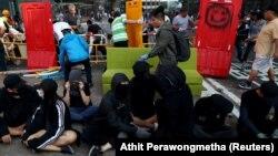 Участники антиправительственных протестов сидят на земле вблизи университета Гонконга, пока местные жители разбирают баррикады. На кадре — события 16 ноября 2019 года.