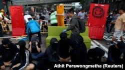 Гонконг университеті қасындағы баррикаданы бұзып жатқан адамдар мен сол жерде отырған үкіметке наразылар. 16 қараша 2019 жыл.