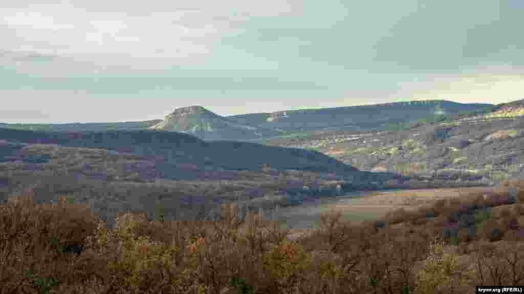 Вдалеке, за лесистым склоном, виднеется Тепе-Кермен – гора-останец с руинами одноименного средневекового города-крепости