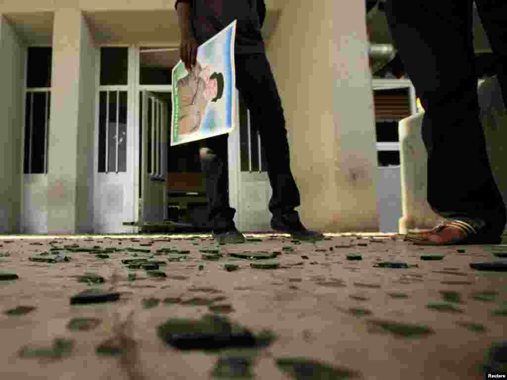 A student carries a picture of Libyan leader Muammar Qaddafi as she stands near pieces of glass from broken windows, which the government said was caused by a Western air strike, at Al-Fatah University in Tripoli on April 14. Photo by Zohra Bensemra for Reuters