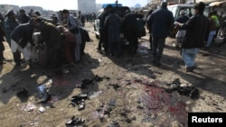 People help clear casualties from the site of a suicide attack at a Shi'ite Muslim gathering in Kabul on December 6.
