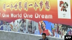 A man sits under a poster for the 2008 Beijing Olympic Games on a street in Xinjiang in August 2008.