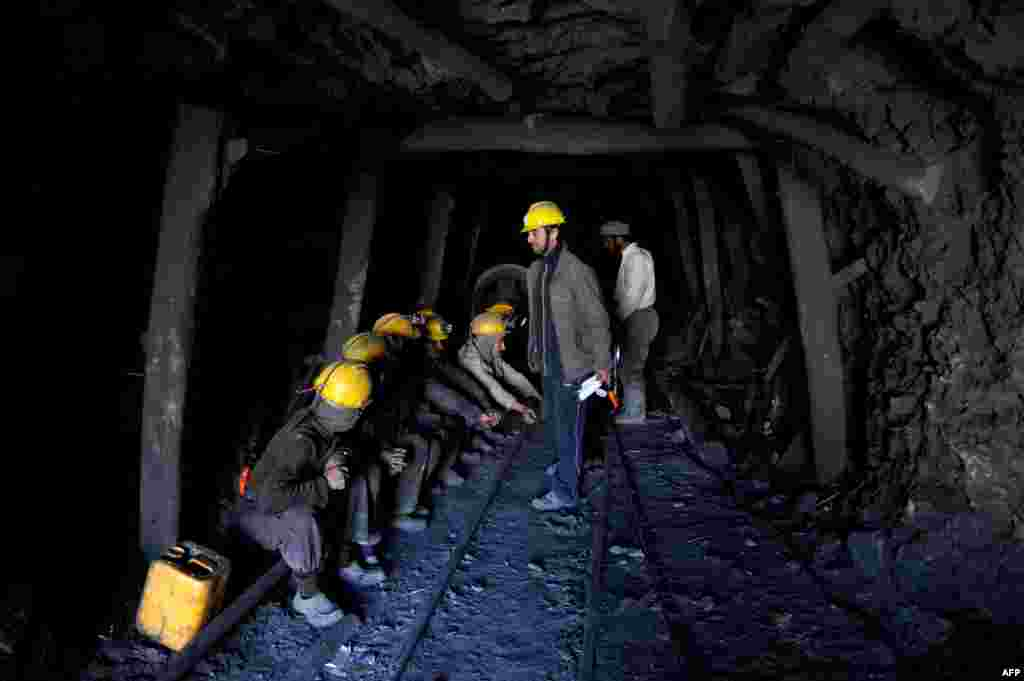 Miners wait to remove the bodies of their colleagues from the mine.