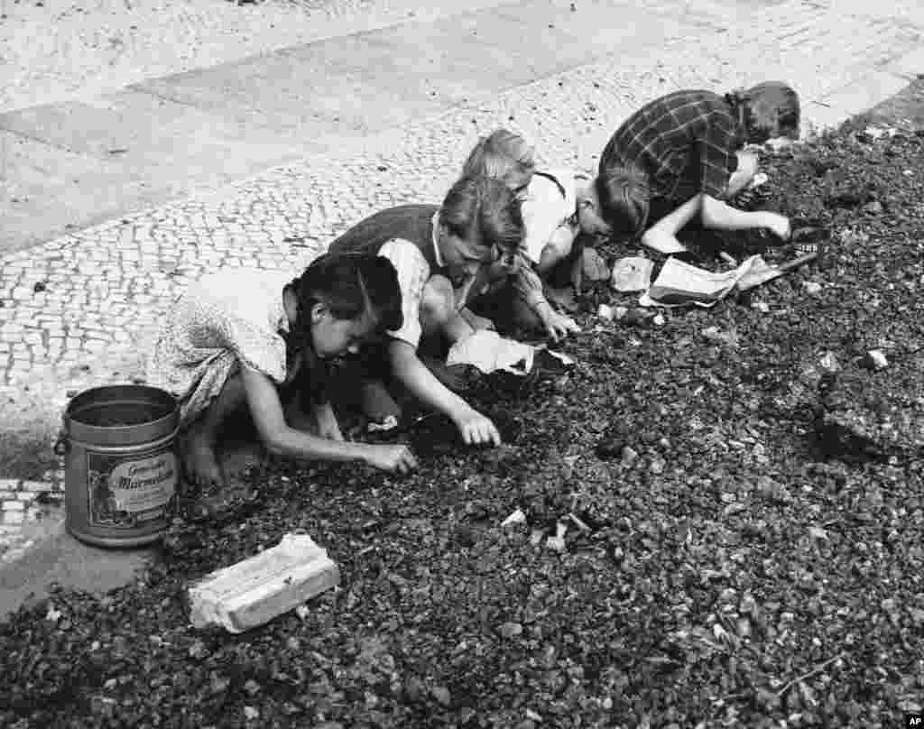 Children sift through a slag heap outside a West Berlin factory for pieces of coal on August 27, 1948. The fuel flown in during the airlift was crucial in keeping factories and utilities operating.