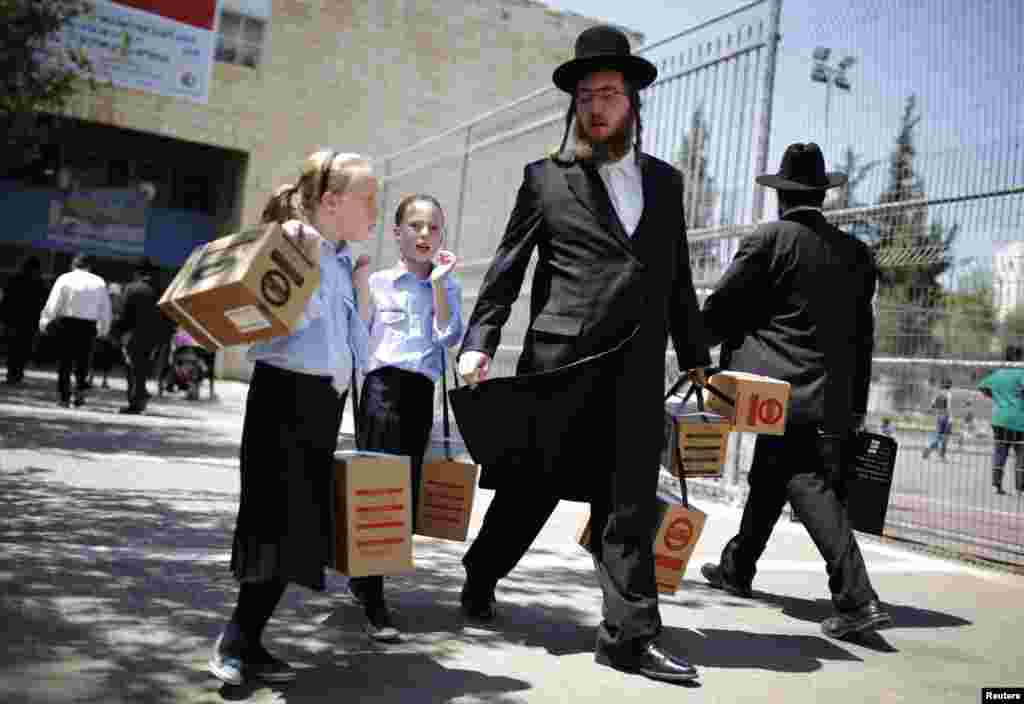 An ultra-Orthodox Jewish man walks out with his children after collecting gas-mask kits at a distribution point in Jerusalem. Thousands of Israelis continue to queue up for gas masks or ordered them by phone, spurred on by fears that any Western military response to last week's alleged chemical-weapons attack in Syria could ensnare their own country in war. (Reuters/Amir Cohen)