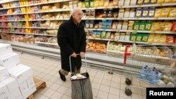 Мужчина в супермаркете проходит рядом с полками, на которых лежит сырная продукция. Москва, 15 января 2015 года.
