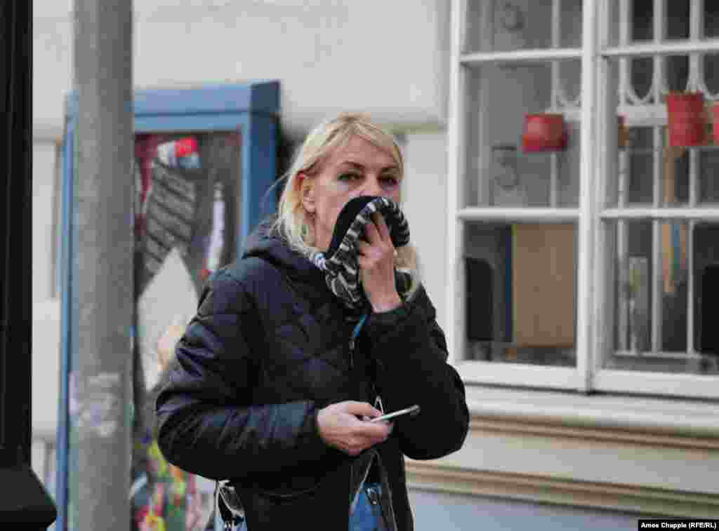 A woman breathing through her scarf in Prague's Mala Strana area.