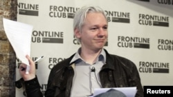 WikiLeaks founder Julian Assange holds a leaked Stratfor document at a news conference in London on February 27.