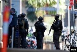 گروهی از افراد پلیس ایالتی و نیروهای ویژه «پورس» در بیرون کافه