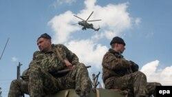 سربازان اوکراینی سوار بر خودروهای زرهی خود در شهر کراماتورسک، در حالی که هلیکوپتری بر فراز آنها در پرواز است.