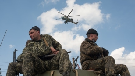 Ukraine -  Ukrainian soldiers sit on their armored vehicle as a helicopter flies past in Kramatorsk, 16 April 2014