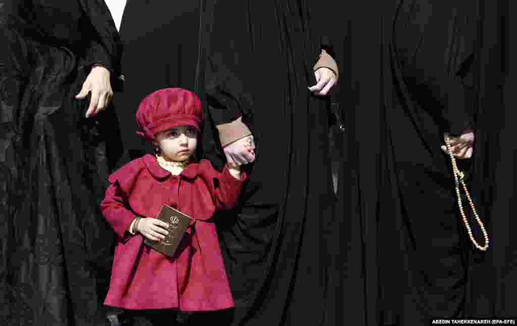 A young Iranian girl holds her mother's hand as they wait in line at a polling station in Shahr-e-Ray, Tehran Province, on February 21. (epa-EFE/Abedin Taherkenareh)