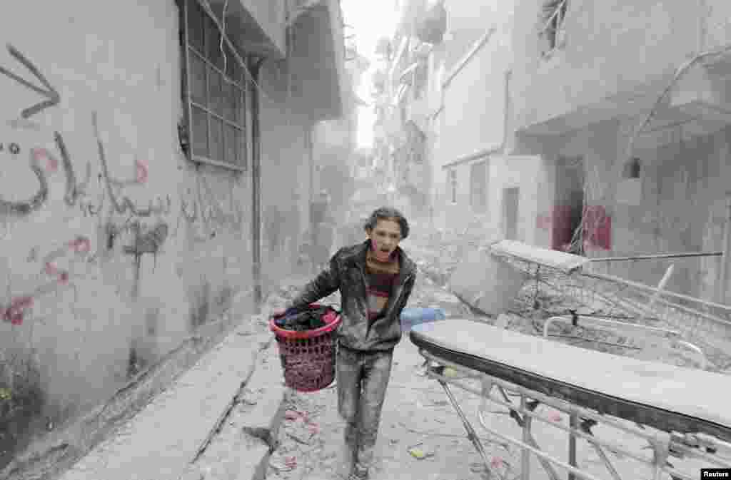 A Syrian boy carries his belongings at a site hit by what activists said was a barrel bomb dropped by government forces in Aleppo's Al-Fardous district on April 2. (Reuters/Rami Zayat)