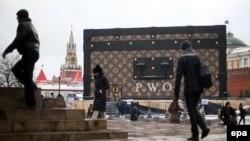Прохожие рядом с инсталляцией Louis Vuitton на Красной площади в Москве. 28 ноября 2013 года.