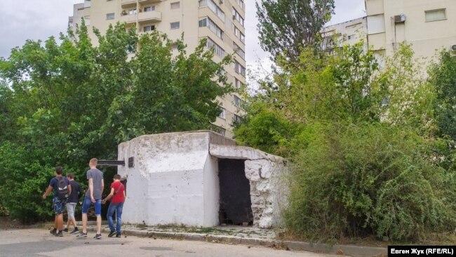 Севастопольские подростки идут мимо ДОТа №31