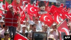 Demonstrators wave the Turkish flag and portraits of Mustafa Kemal Ataturk.