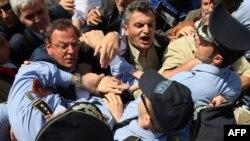 Туркање меѓу полицијата и опозициски пратеници пред зградата на Државната изборна комисија во Тирана на 18 мај 2011 година.