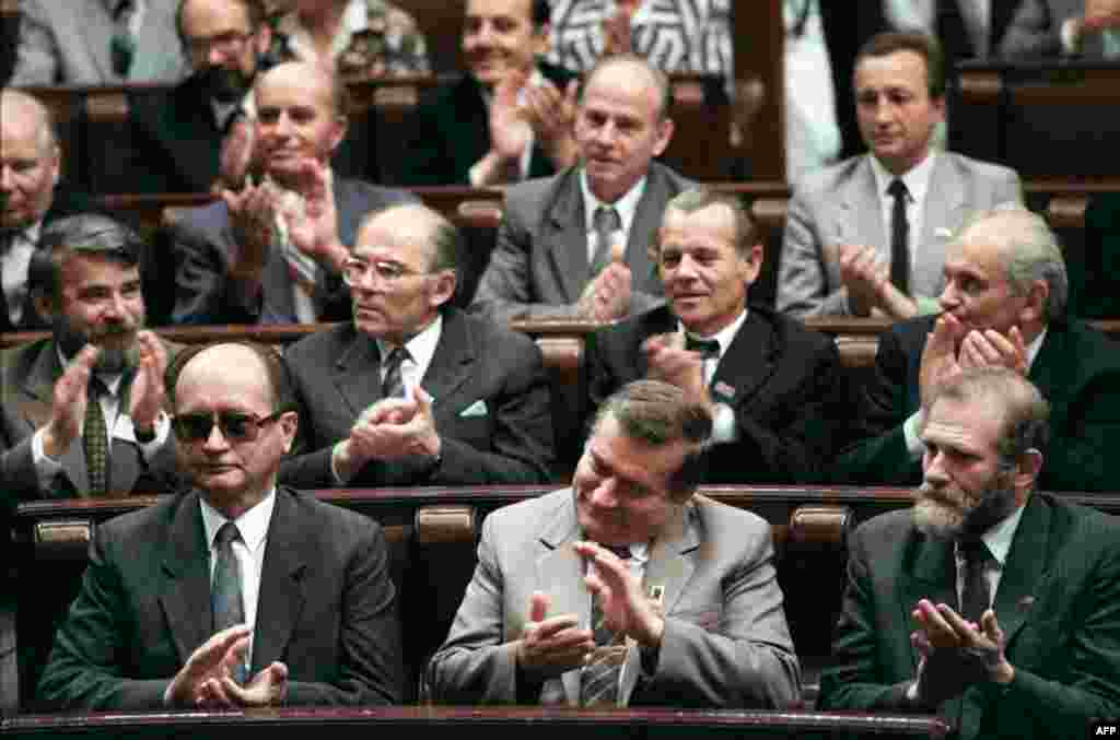 Jaruzelski, Solidarity leader Lech Walesa, and Solidarity adviser Bronislaw Geremek (front row, left-to-right) applaud during the first meeting in 50 years of Poland's parliament, the Diet, in Warsaw on July 4, 1989.
