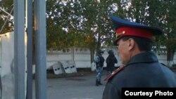 Павлодар түрмесінің алдында тұрған полиция қызметкері және арнайы жасақ өкілдері.
