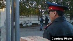 Полицейский на фоне сотрудников в бронежилетах и камуфляжной форме. Фото 15 сентября 2014 года прислали родственники заключенных, содержащихся в тюрьме Павлодара.