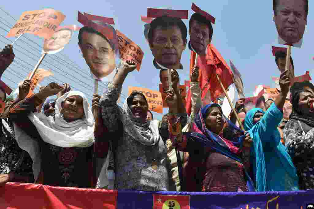 Pakistani workers carry cutouts of images of Pakistani political-party leaders as they shout slogans during a May Day rally to mark International Labor Day in Lahore on May 1. (AFP/Arif Ali)