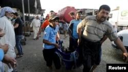 Адамдар базарда болгон жардырууда набыт болгон адамдын жасатын алып баратышат. Багдад, 13-август 2015