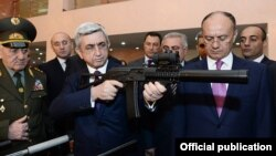 Armenia - President Serzh Sarkisian examines an Armenian-made rifle during a visit to the Defense Ministry in Yerevan, 18Apr2014.
