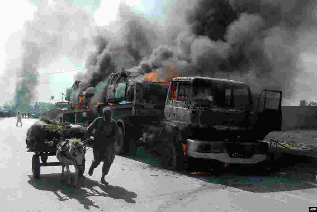 A man leads his donkey-cart past a burning trailer truck transporting NATO vehicles following an attack by gunmen in the Wazir Dhand area of Khyber province, Pakistan, on May 5. (AFP)