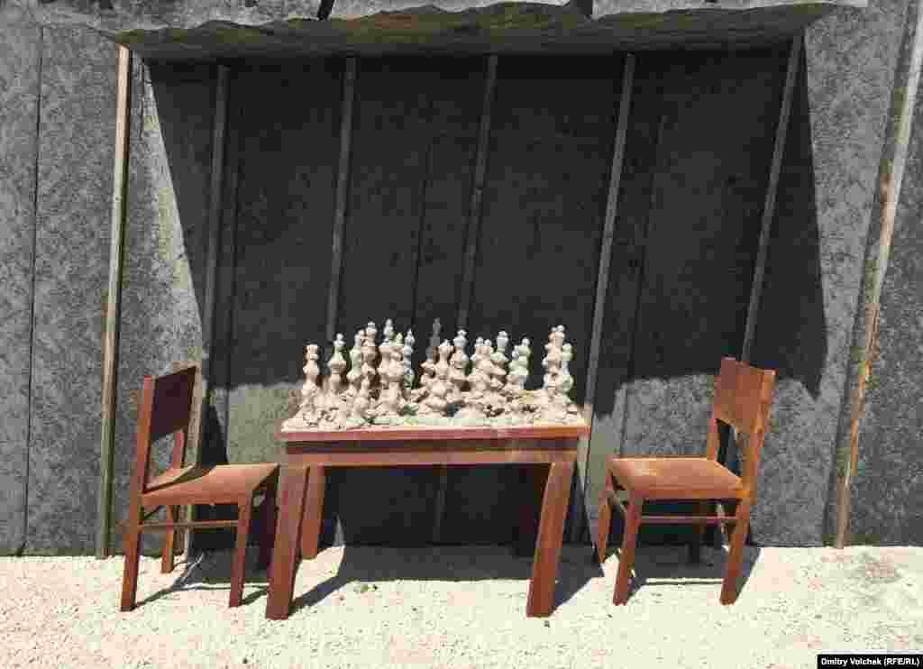 Шахматные фигуры превратились в песок, а стулья, на которых сидели игроки, скособочились.