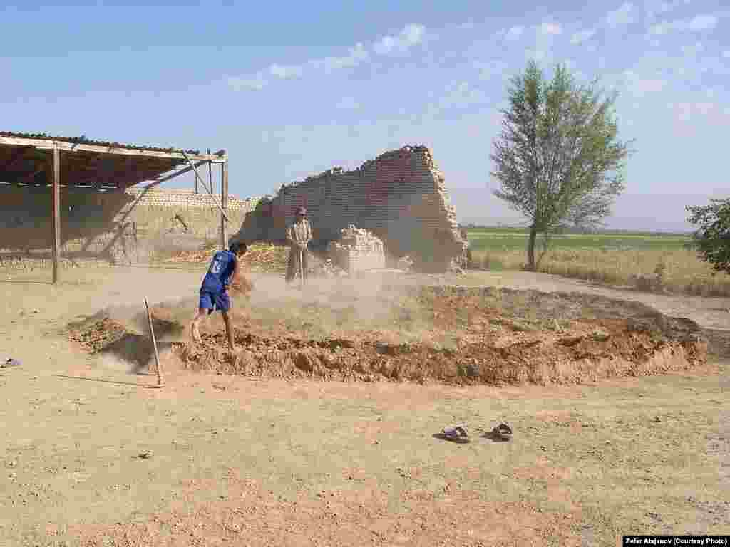 Kyrgyz children prepare the mud used to make clay bricks.