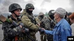 Местные жители общаются с украинскими военными на захваченном ими блокпосту около Славянска, 2 мая 2014 года.
