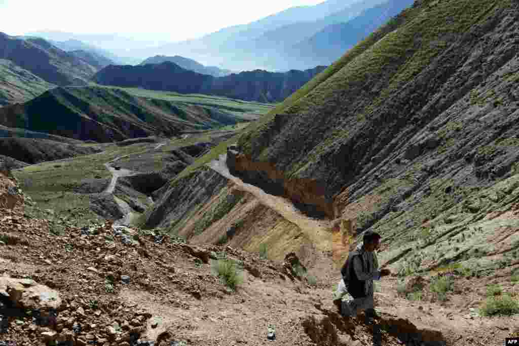 Afghan miner Morad Ali walks on a mountainside near the village of Qara Zaghan in Baghlan Province.