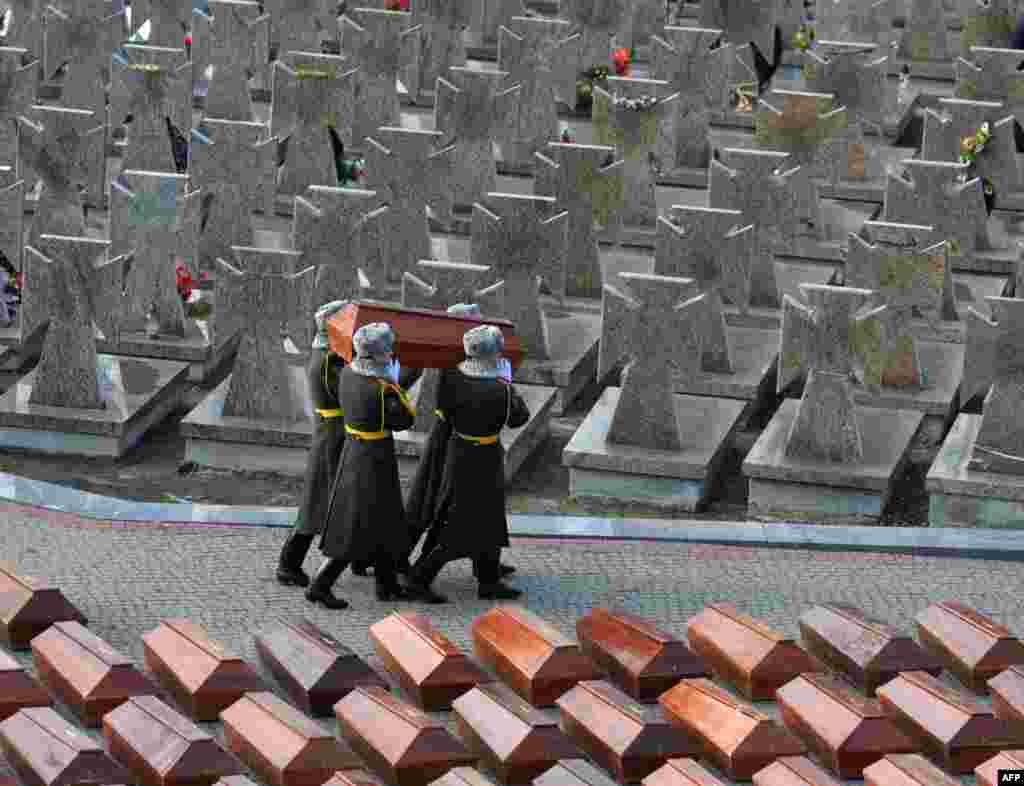 An honor guard carry coffins with human remains during a reburial ceremony in Lviv, Ukraine. The remains of more than 500 apparent victims of the Soviet regime were reburied on February 3 at a cemetery in the western Ukrainian city. The bones of 511 people -- 67 of them children -- were found in two separate locations by construction workers and residents in 2014-2015. (AFP/Yuriy Dyachyshyn)