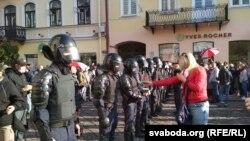 Арнайы жасақ қызметкеріне Беларусь Конституциясын ұсынып тұрған демонстранттардың бірі.
