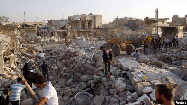 Men search for bodies of people after a Syrian air strike on Azaz.