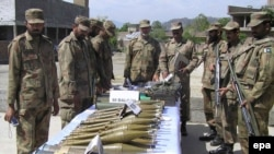 Pakistani Army soldiers show arms and ammunition recovered during operations against Taliban militants in Charbagh.