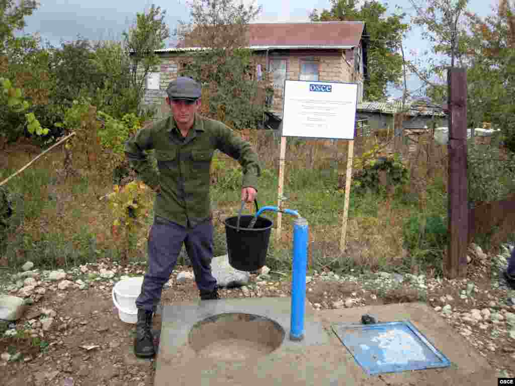 A villager in Georgia collects water from a source provided by an OSCE development project.
