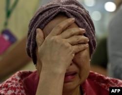 Malaysia Airlines ұшағында қаза тапқан жолаушының туысы жылап отыр. Малайзия, 18 шілде 2014 жыл.
