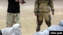 A capture from the Islamic State video purporting to show the execution of what it describes as two Russian spies.