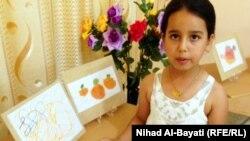 كركوك: فنانة صغيرة مع لوحاتها