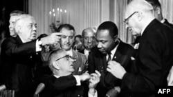 Президент США Линдон Джонсон дарит борцу за права чернокожего меньшинства Мартину Лютеру Кингу ручку, которой он только что подписал Билль о гражданских правах