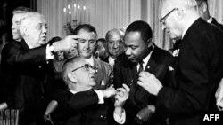 """Президент США Линдон Джонсон пожимает руку Мартину Лютеру Кингу после подписания """"Закона о гражданских правах"""" в стенах Белого дома. Вашингтон, 2 июля 1964 года."""
