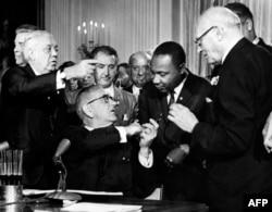 Прэзыдэнт ЗША Ліндан Джонсан уручае Кінгу пяро, якім падпісаў гістарычны Акт аб грамадзянскіх правах, 2 ліпеня 1964