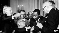 الرئيس جونسون يتحدث الى لوثر كنغ أثناء توقيع وثيقة الحقوق المدنية