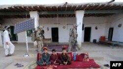 د افغانستان د خوست په سبرۍ ولسوالۍ کې امریکايي ځواکونه د کور په کور پلټنو په مهال د وسلو لټون کوي.